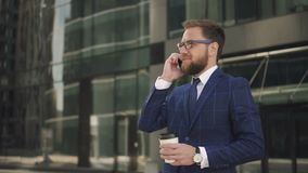 Young businessman with coffee in hand talking on phone standing near company office. stock video footage