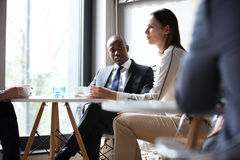 Young businessman with colleagues having coffee in office Royalty Free Stock Image