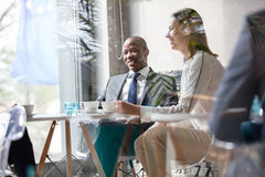 Young businessman with colleagues having coffee at table in office Royalty Free Stock Photos