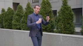 Young businessman comes with wireless earphones and aggressively leads a discussion on a video call on smartphone stock video footage