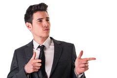Young businessman confidently pointing fingers to. A side, wearing suit isolated in white background Royalty Free Stock Image
