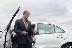 Young Businessman Consulting His. A young ethnic businessman consults his notes while standing next to his car Stock Photos