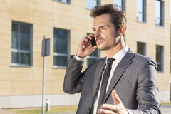 Young businessman conversing on cell phone against office building Royalty Free Stock Photos