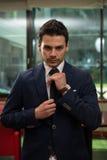 Young Businessman Correcting A Tie Stock Photos