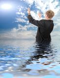 Young businessman costs in water and asks from sun Stock Image