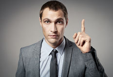 Young businessman criticizing on gray Royalty Free Stock Photos