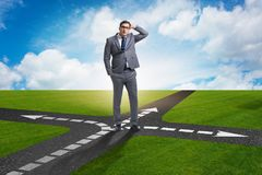 The young businessman at crossroads in uncertainty concept. Young businessman at crossroads in uncertainty concept Royalty Free Stock Images