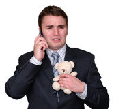 Young Businessman Crying on Cell Phone, clutching Teddy Bear. Young businessman clutching a small teddy bear, crying and talking on a cell phone. Isolated on stock image