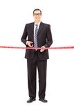 Young businessman cutting a red tape Royalty Free Stock Photography