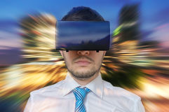 Young businessman is in 3D simulation of city. He is wearing virtual reality headset Royalty Free Stock Image