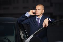 Young businessman in dark blue suit calling on cell phone leaning on his car. Young businessman calling on cell phone leaning on his car  Stylish trendy male royalty free stock photo