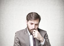 Bearded businessman in doubt,. Young businessman with dark hair and a beard wearing a suit is thinking. Concept of doubt and choice in decision making Stock Images