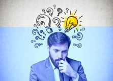 Bearded businessman in doubt, answer search. Young businessman with dark hair and a beard wearing a suit is thinking. A concrete wall background with question Stock Photos