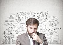 Bearded businessman in doubt, business plan. Young businessman with dark hair and a beard wearing a suit is thinking. A concrete wall with a business plan sketch Stock Photos