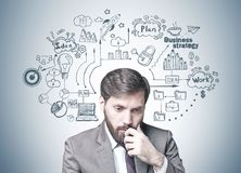 Bearded businessman in doubt, business strategy. Young businessman with dark hair and a beard wearing a suit is thinking. A gray wall with a business strategy Stock Photography