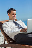 Young businessman on a deck chair using his computer Stock Photography
