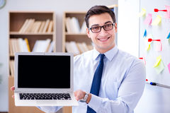The young businessman demonstrating the screen of his laptop Royalty Free Stock Photography