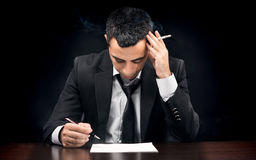 Young Businessman In Depression Smoking And Reading Contract Before Signing stock photos