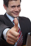 Young businessman at desk shows thumb up Stock Image