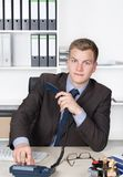 Young businessman is dialing a number at the phone Royalty Free Stock Images