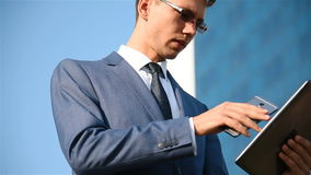 Businessman with tablet talking on cellphone stock footage