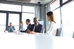 Young businessman discussing with female colleague in board room Royalty Free Stock Photos