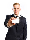 Young businessman doing his introduction. Half length portrait of a young businessman doing his introduction, focus on the card and hand royalty free stock image
