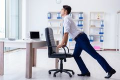 The young businessman doing sports stretching at workplace. Young businessman doing sports stretching at workplace Royalty Free Stock Images