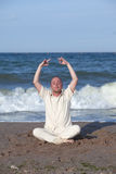 Young businessman doing yoga on a beach Stock Image