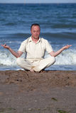 Young businessman doing yoga on a beach Stock Images