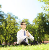 Young businessman doing yoga exercise seated on a grass in a par Royalty Free Stock Photos