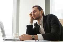 Young businessman dozed in front of laptop at work. Royalty Free Stock Image