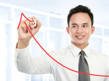 Young businessman drawing statistic. Arrow on screen with a pen in the office Royalty Free Stock Images