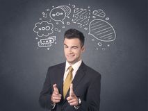 Businessman with speech bubbles. Young businessman with drawn speech bubbles over his head Royalty Free Stock Photography