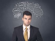 Businessman with speech bubbles. Young businessman with drawn speech bubbles over his head Stock Images