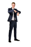 Young businessman dressed in a suit points to at watch Stock Images
