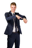 Young businessman dressed in a suit points to at watch Stock Photo