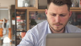 Young businessman drink coffee at the cafe. Young bearded businessman drinking coffee at the cafe. Close up of blond caucasian man sitting at the table with