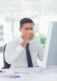 Young businessman drinking coffee at his desk Royalty Free Stock Photography