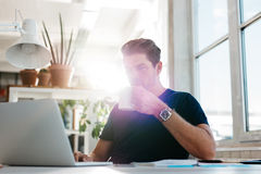 Young businessman drinking coffee and looking at laptop Stock Image