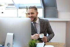 Young businessman drinking coffee in office while typing on computer royalty free stock images