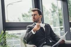 Young businessman drinking coffee while sitting. In armchair Stock Images