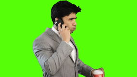 Young businessman drinking coffee while talking on cell phone stock video