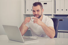 Young businessman drinking coffee, toned Royalty Free Stock Images
