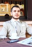 Young businessman drinking a cup of coffee while sitting Royalty Free Stock Image