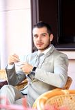 Young businessman drinking a cup of coffee while sitting Stock Images