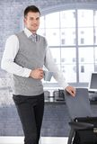 Young businessman drinking tea in office smiling Royalty Free Stock Image