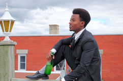 Young businessman drinking wine bottle on roof success suit and tie Stock Photo