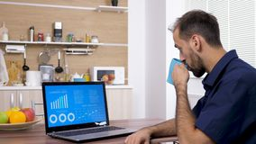Young businessman drinks coffee and looks at data and chart analysis. On his laptop in the kitchen stock footage