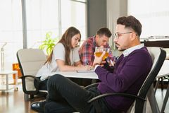 Young businessman drinks tea while his collegues on backgroung work hard. Boss relax in office. Teamwork concept Stock Photos